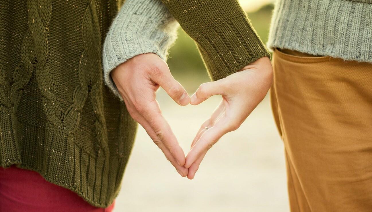 Ett par som gemensamt skapar ett hjärta med sina händer.