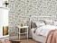 Ett sovrum med en vit kakelugn, brädgolv och en säng med fluffiga ljusa lakan. Väggarna är täckta i en krämfärgad tapet med slingrande blomsterrankor.