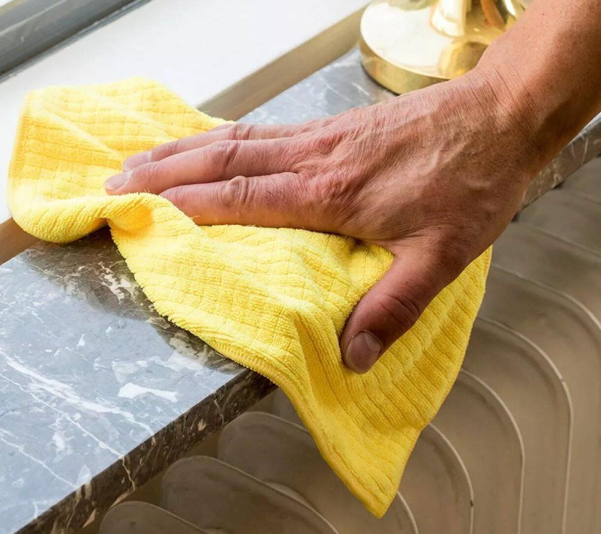 Kvinna torkar av fönsterkarm med mjuk mikrofiberduk.