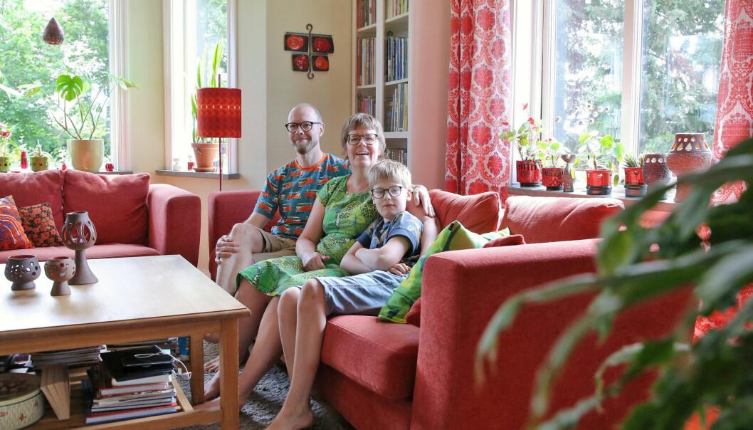 Familjen Holgersson sitter i sin röda soffa.