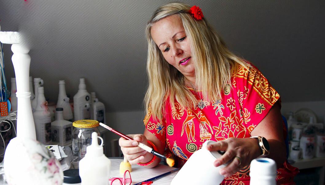 Hanna målar någon form av porslin iklädd röda färgstarka kläder