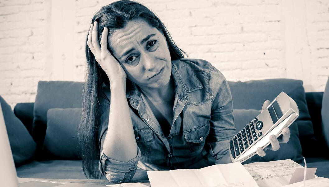 Kvinna sitter med en dator och miniräknare och ser stressad och ledsen ut