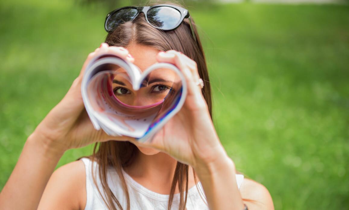 Kvinna tittar genom en tidning formad som en hjärtformad kikare.