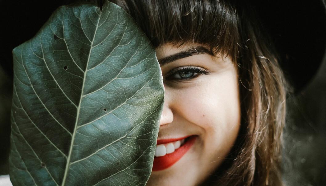 Kvinna kikar fram bakom ett löv