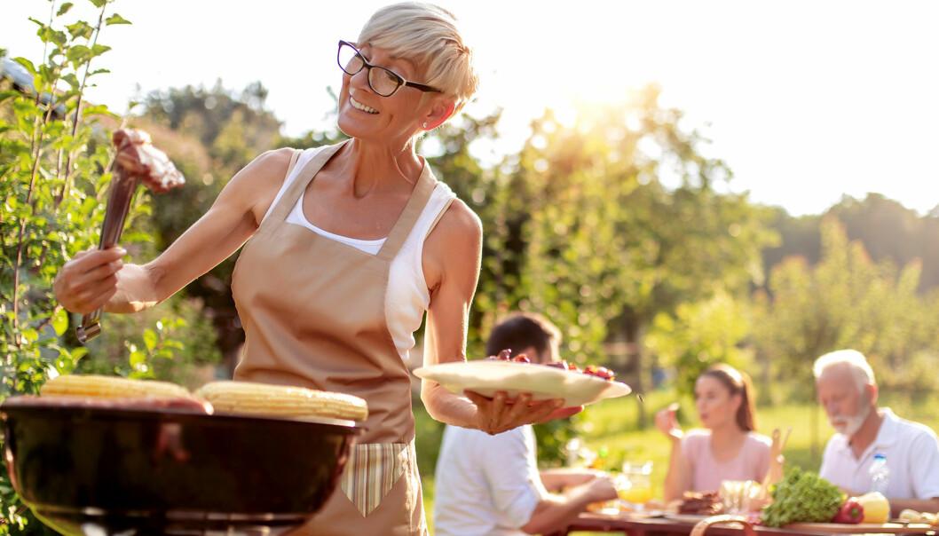 Kvinna står vid grillen och tittar skeptiskt på en köttbit
