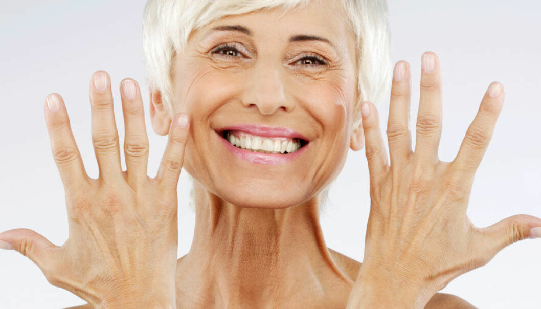 En kvinna ler och visar upp sina friska händer.