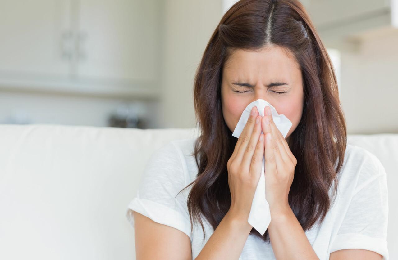 Förkyld kvinna snyter sig i en näsduk.