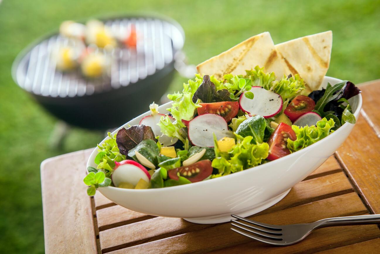 Fräsch sallad i vit skål på ett bord ute i en trädgård.