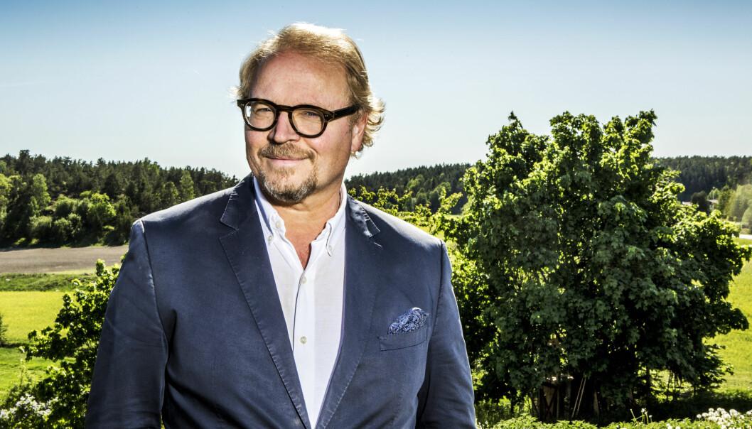 Fredrik Lindström kikar in i kameran med ett vetande leende. Han har blå kostym och står mitt i ett grönt sommarlandskap