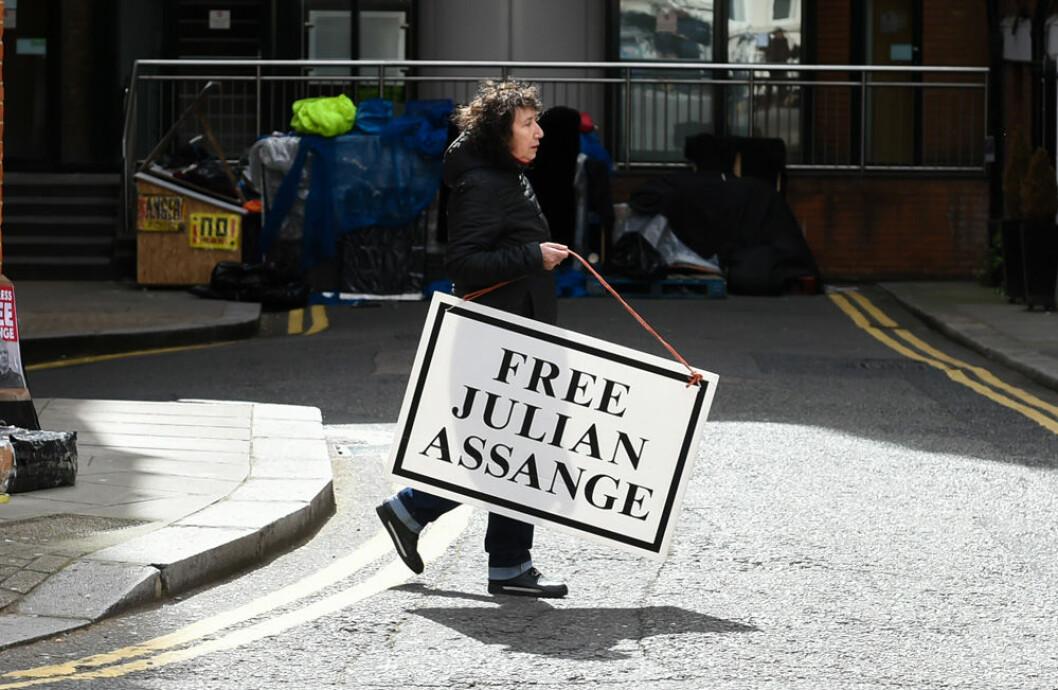 Kvinna som håller i en skylt om att frige Julian Assange.