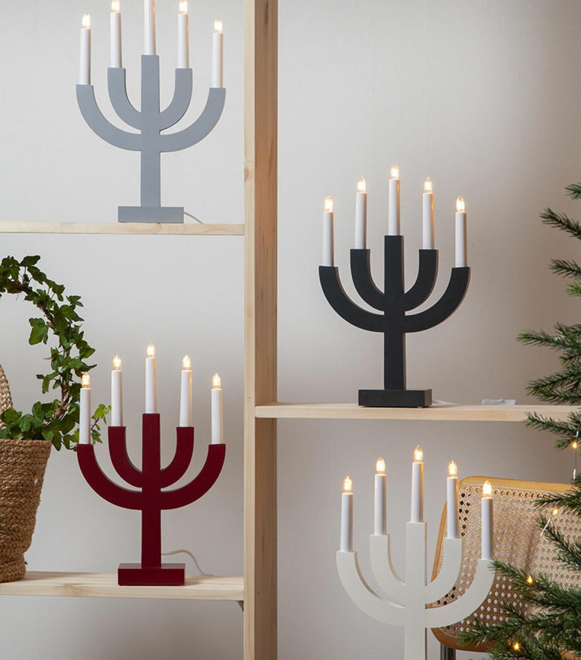 Fyra adventssljusstakar i olika färger.