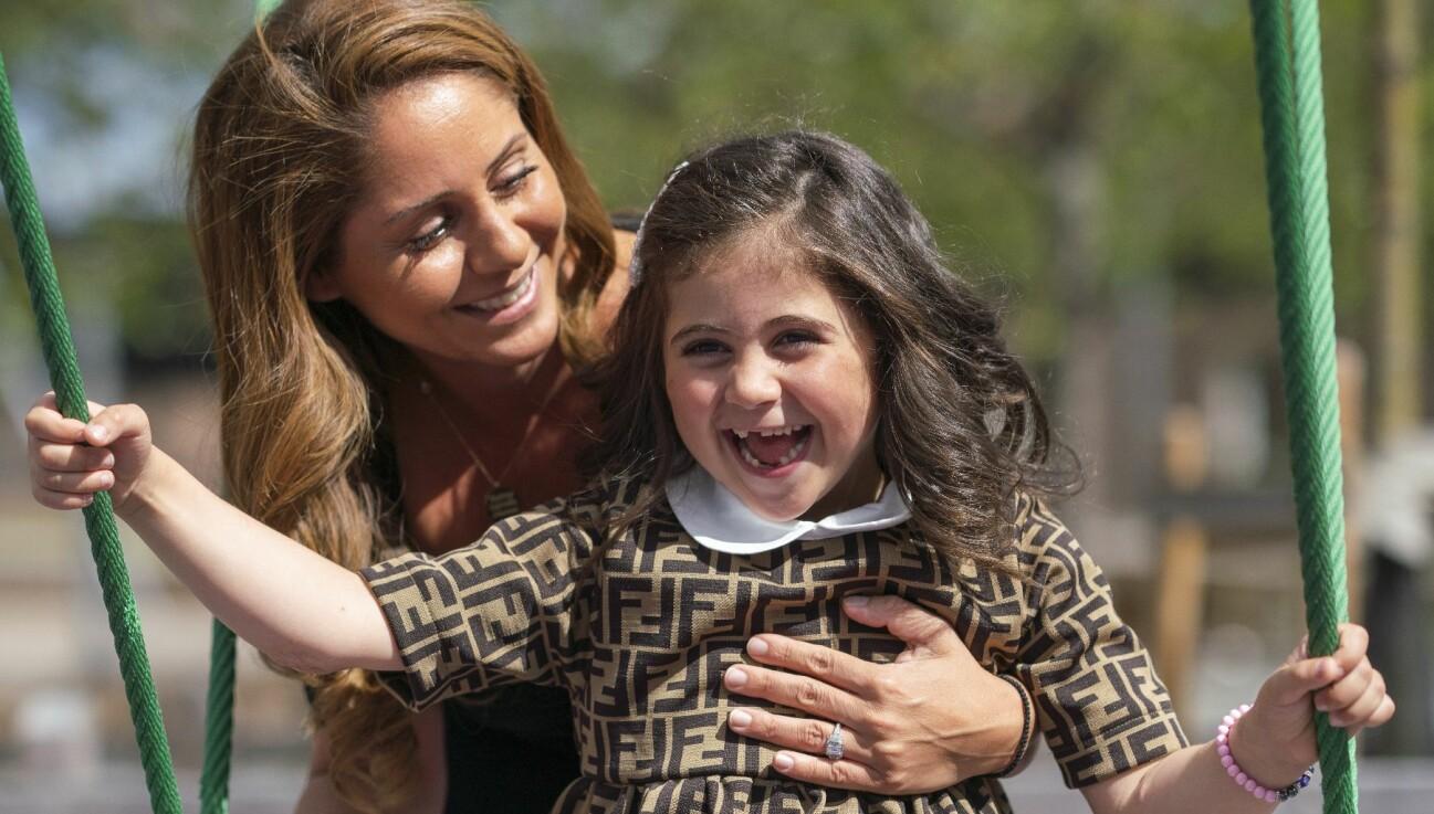 Gabriella och mamma Jenny ser båda glada ut, dottern på en gunga.