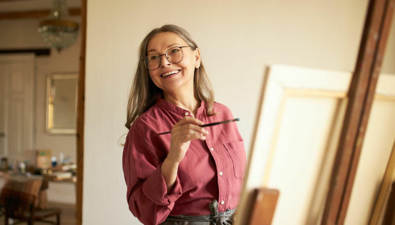 Glad kvinna i mogen ålder målar tavla.