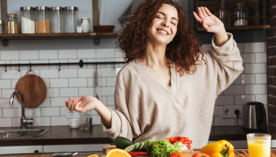 Glad kvinna lagar mat i ett kök.