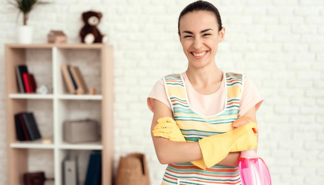 Glad kvinna med diskhandskar och sprayflaska i vardagsrummet.