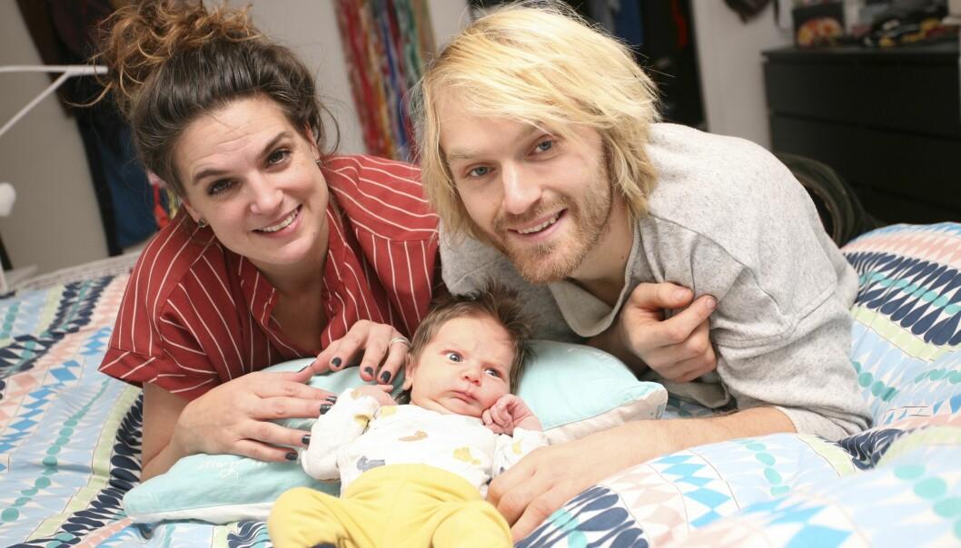 Glada föräldrarna Nadja och Marcus lutar sig över sängen och mirakelbabyn Noor.