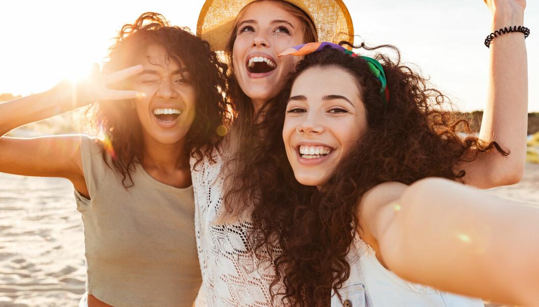 glada tjejer på en strand sommar
