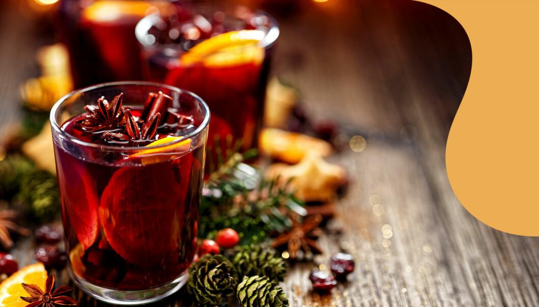 Glögg i glas dekorerat med apelsinskiva och kryddor.