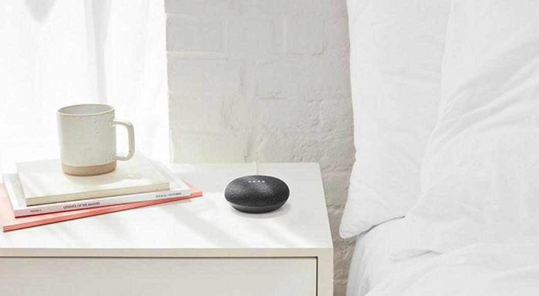 En bild på Google Home Mini på ett sängbord i ett sovrum.