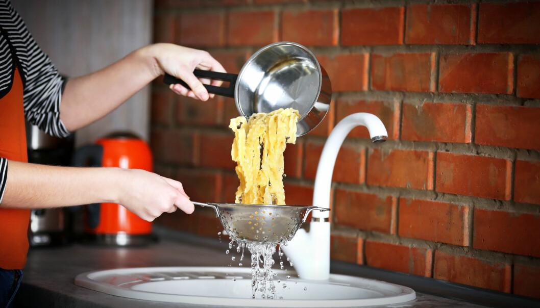 Person häller pasta genom durkslag ner i vasken.