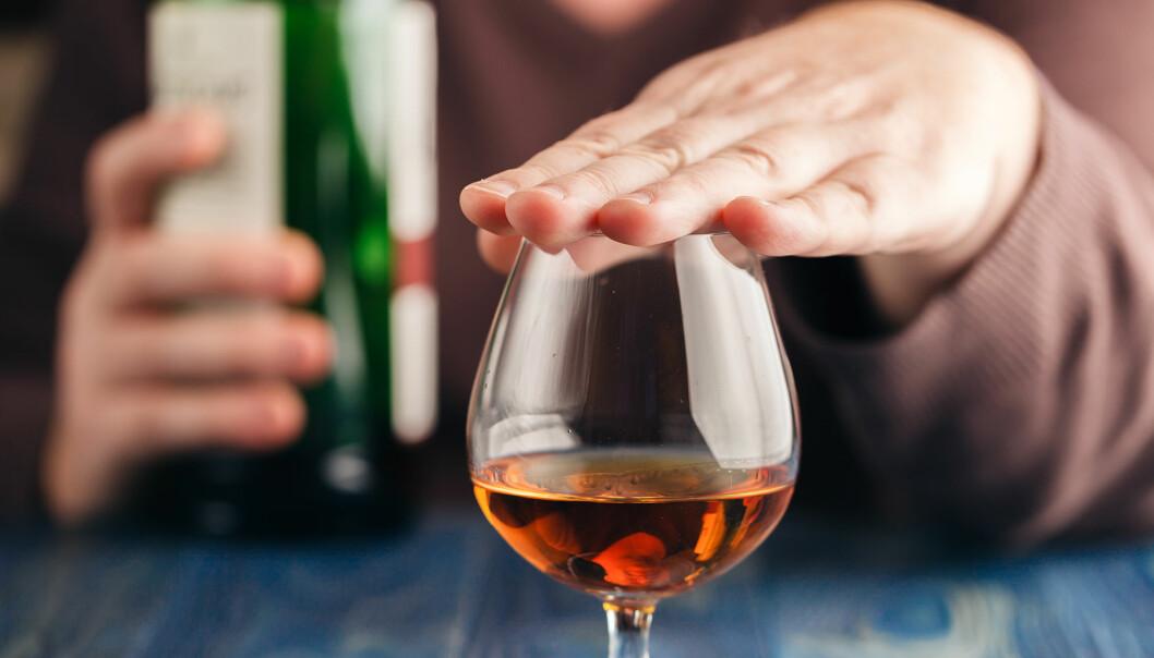 Person håller för glas med alkohol i