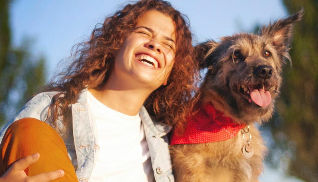 Skrattande kvinna tillsammans med en hund
