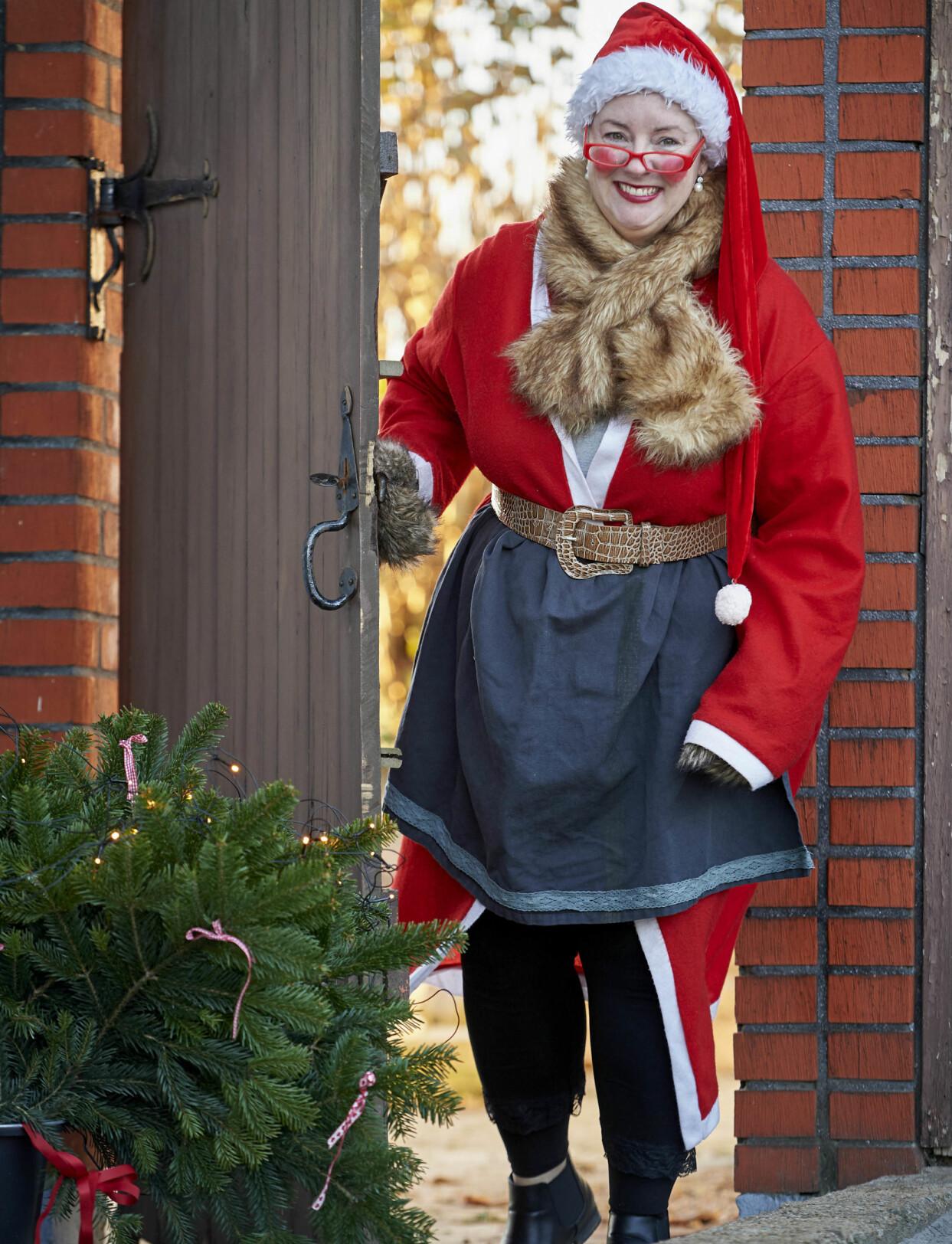 Ulrika, utklädd till Tomtemor, kikar leende fram genom en trädörr.