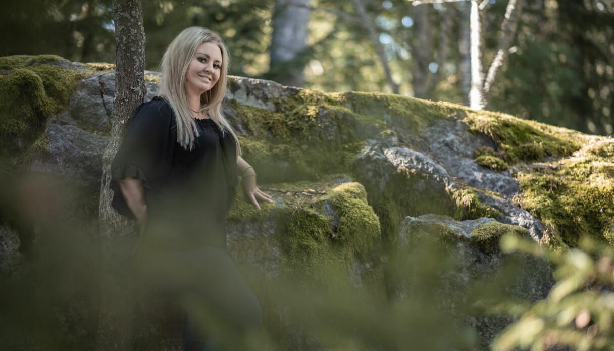 Heidi Mattsson som drabbades av hjärtinfarkt står och poserar i skogen.