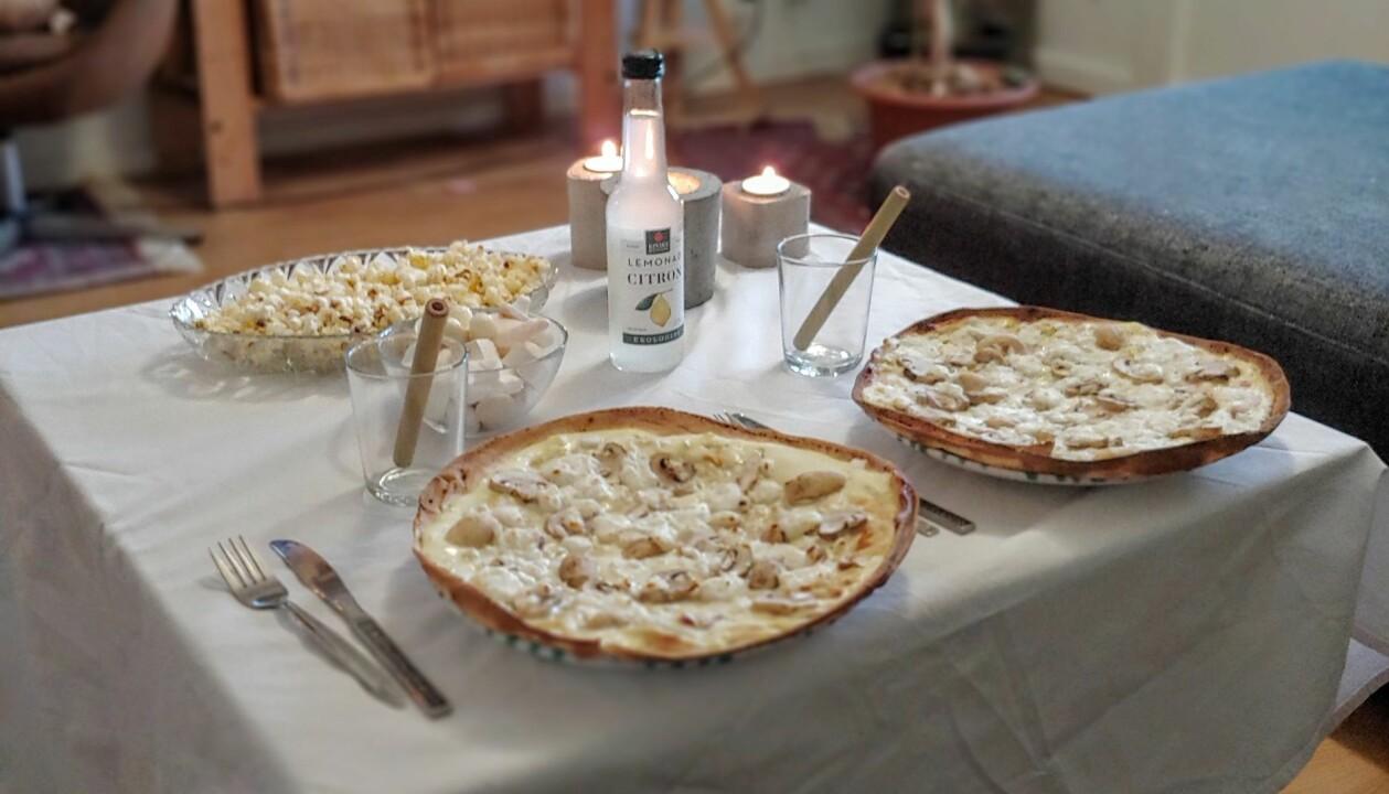 Ett bord med vit duk, två ljusa maträtter och tända ljus.
