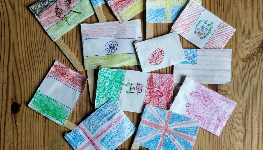 Olika länders flaggor ritade på små lappar fäst på glasspinnar.