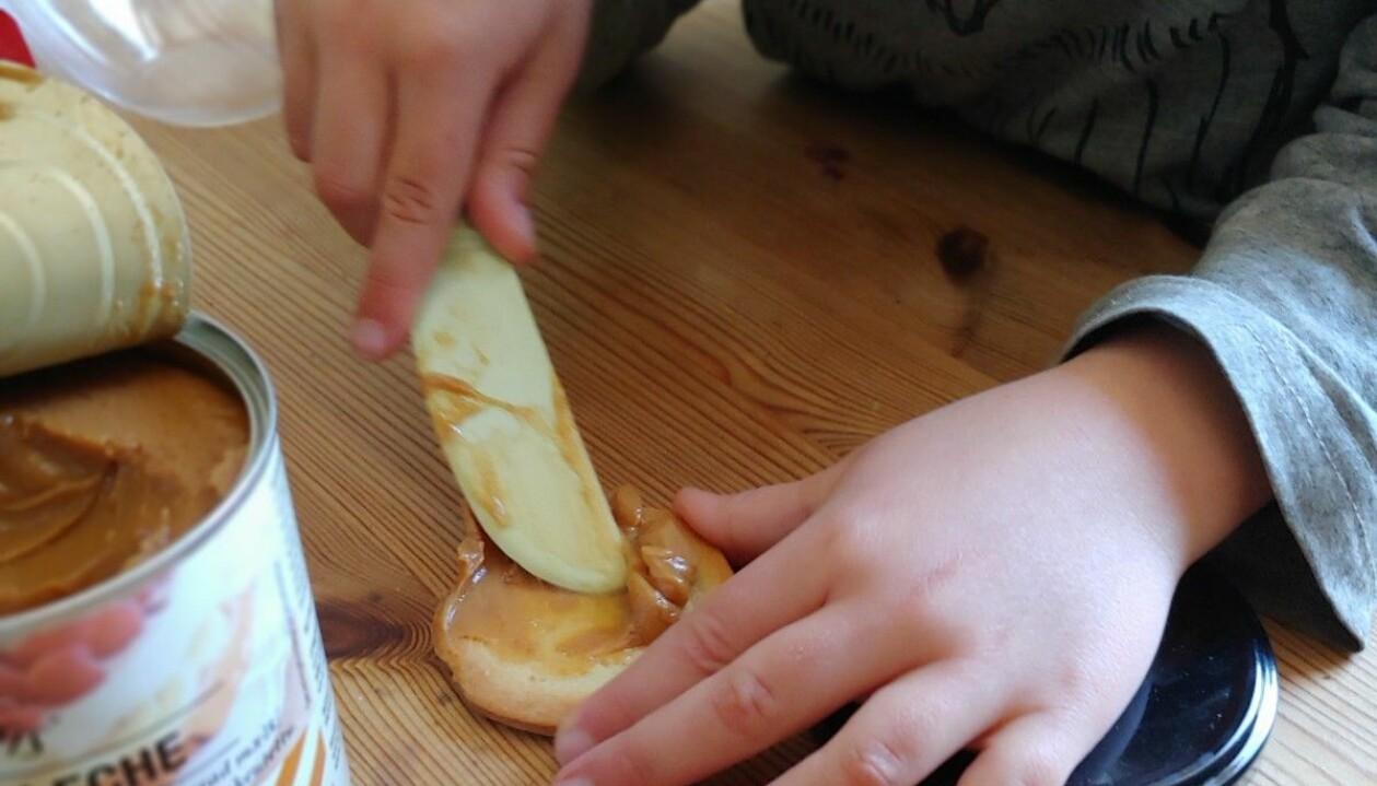 Ett av barnen brer dulce de leche på en kaka.