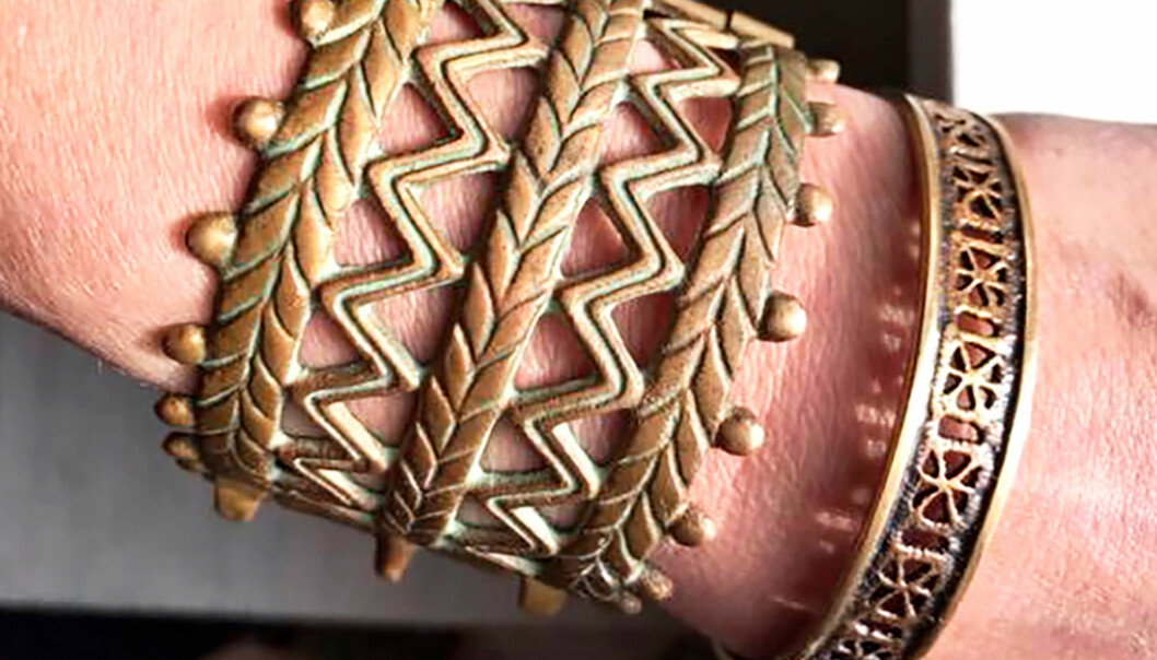 Två äldre armband i brons på en handled