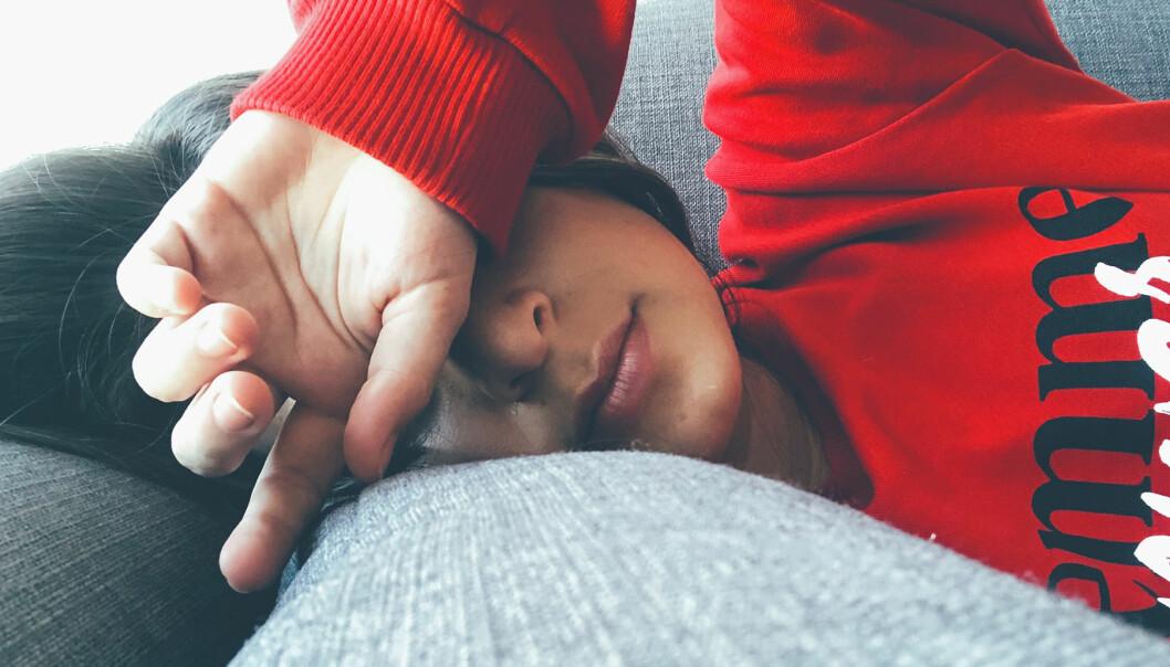 Kvinna ligger i soffa och håller sig för pannan