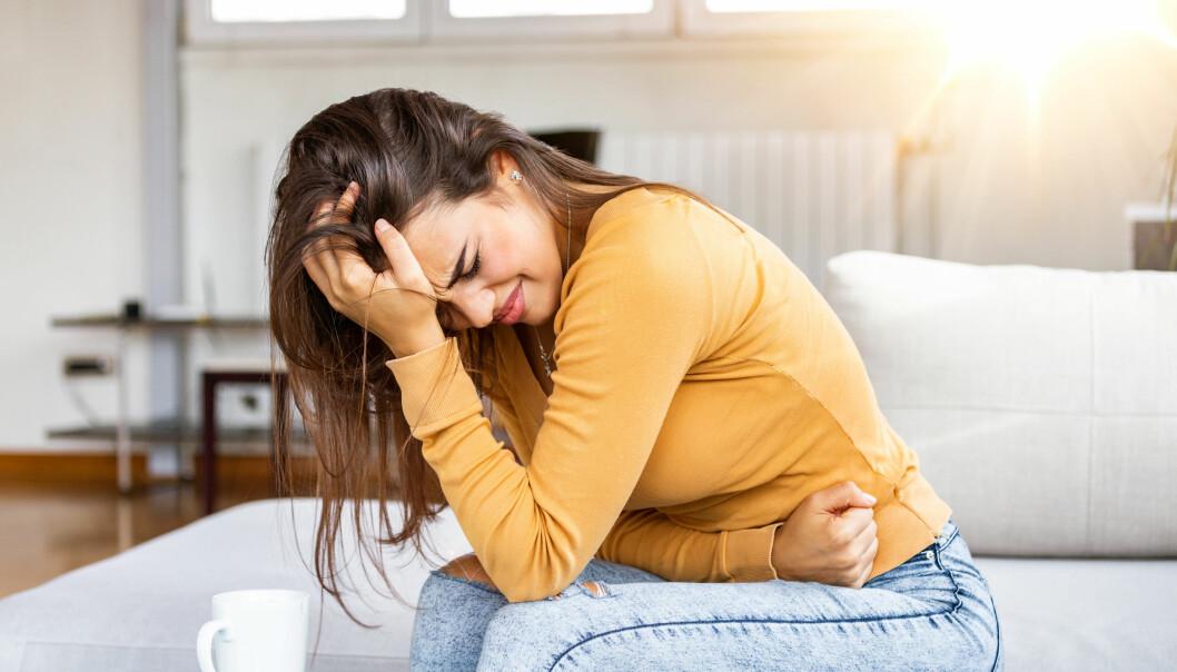 Kvinna ser ut att ha ont i magen, kanske är det ibs?