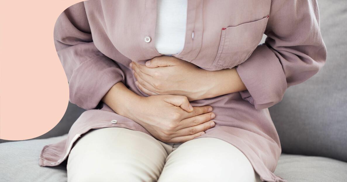 En kvinna med magsmärtor på grund av IBS håller sig för magen.