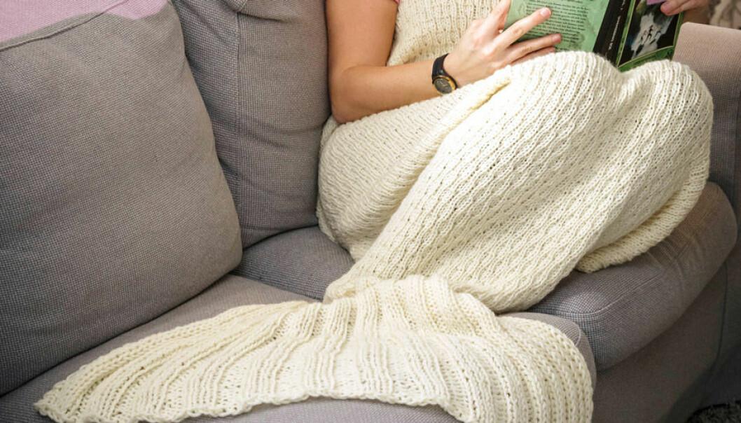 Kvinna sitter i soffa med sjöjungfrupläd.