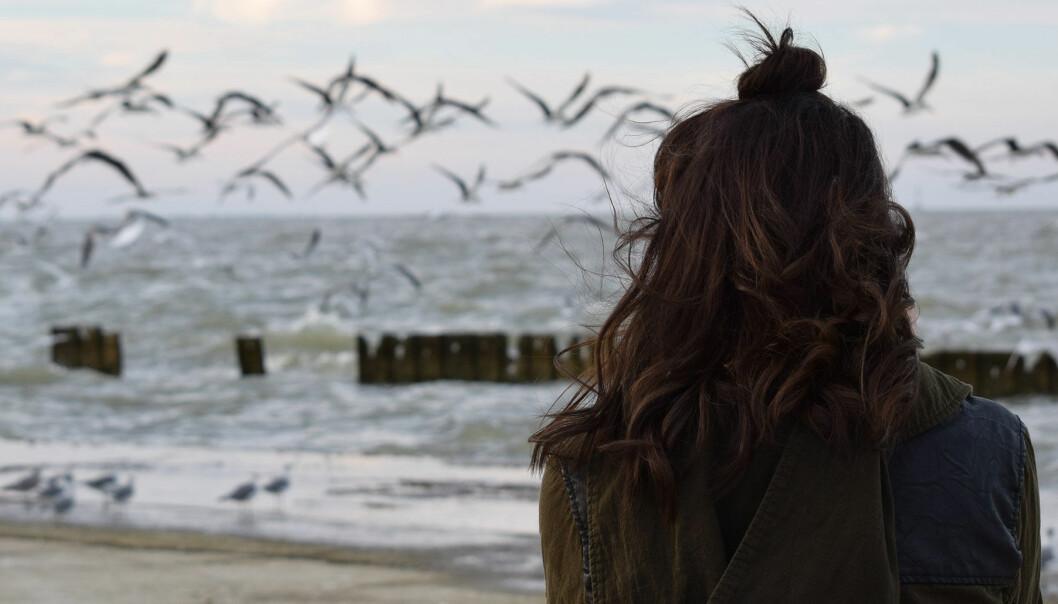 Kvinna tittar ut mot vattnet.