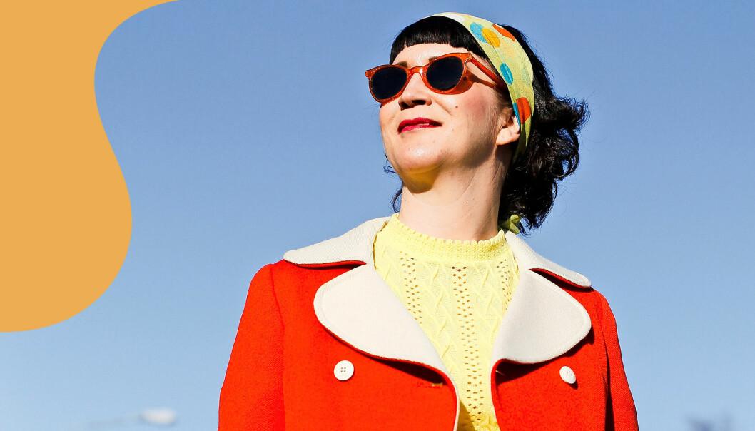 Linda iklädd vintage-kappa i rött tittar mot solen