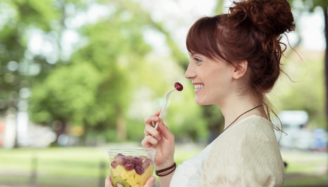 Kvinna äter frukt ur en burk