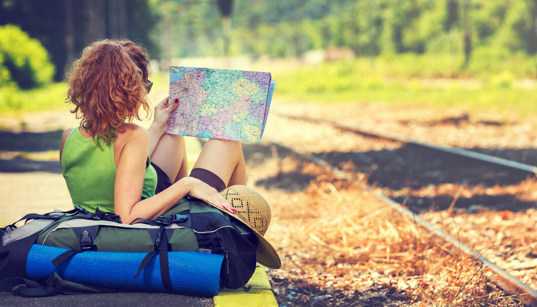 Kvinna sitter på perrong och tittar på en karta