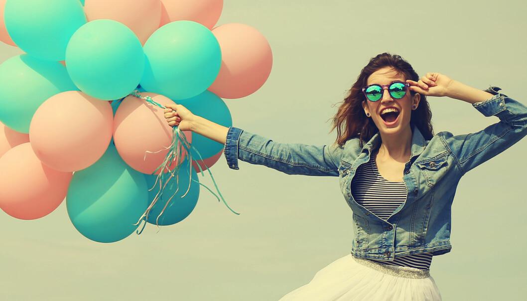 Glad kvinna med ett gäng ballonger i handen