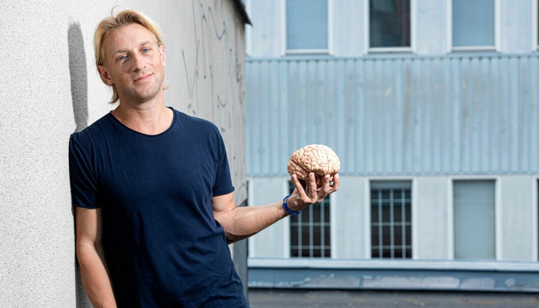 Anders Hansen lutar sig mot en husvägg och håller en modell av en hjärna i handen