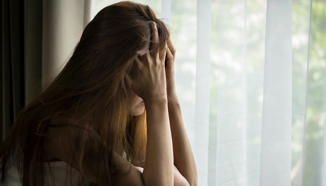 Tonårstjej sitter i ett fönster och ser ledsen ut