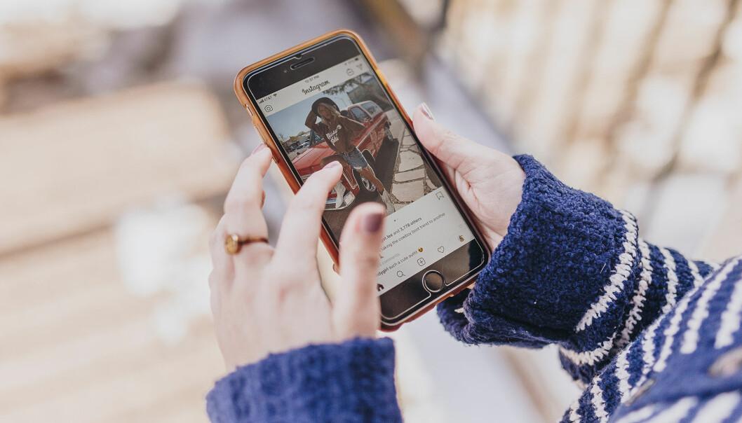 Kvinna kollar Instagram på en telefon