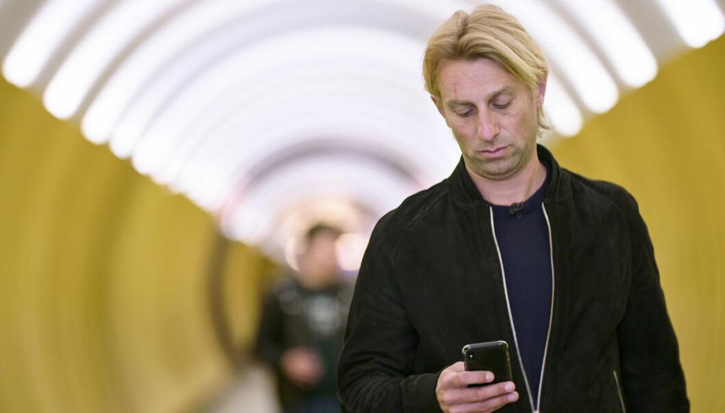 Anders Hansen, aktuell med Din hjärna på SVT, med en telefon i handen