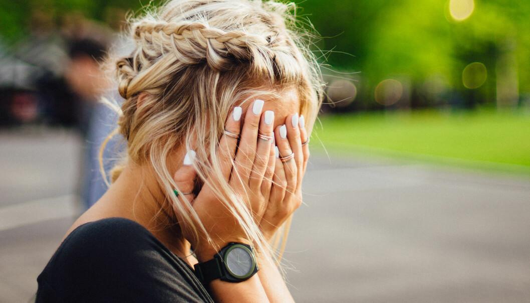 Kvinna håller händerna för ansiktet i frustration
