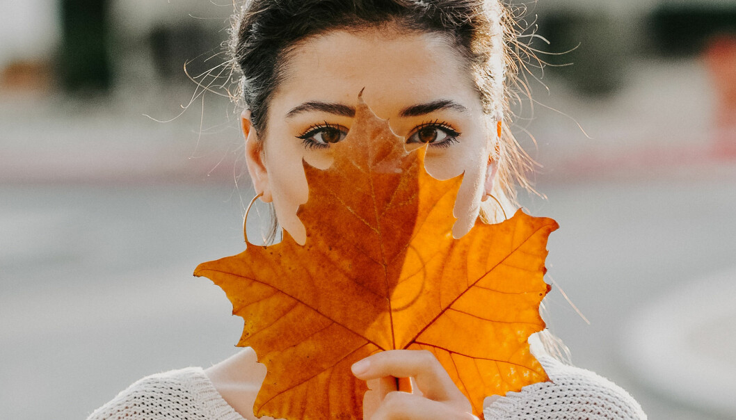Kvinna håller ett stort blad framför ansiktet