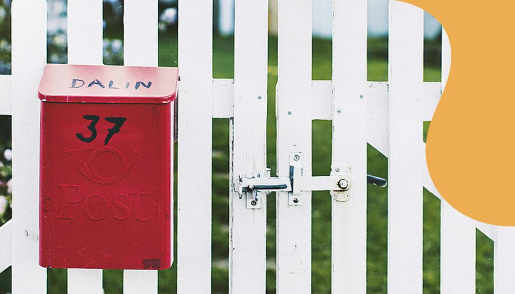 Röd brevlåda sitter på staket.
