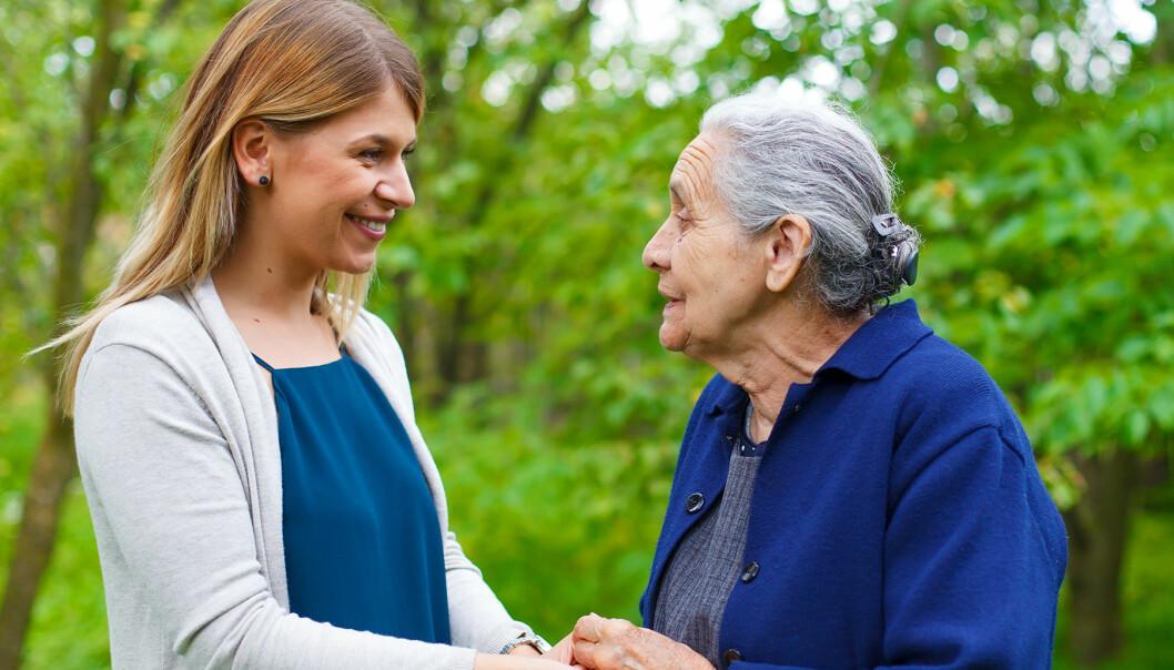 Kvinna håller en äldre dement kvinna i handen