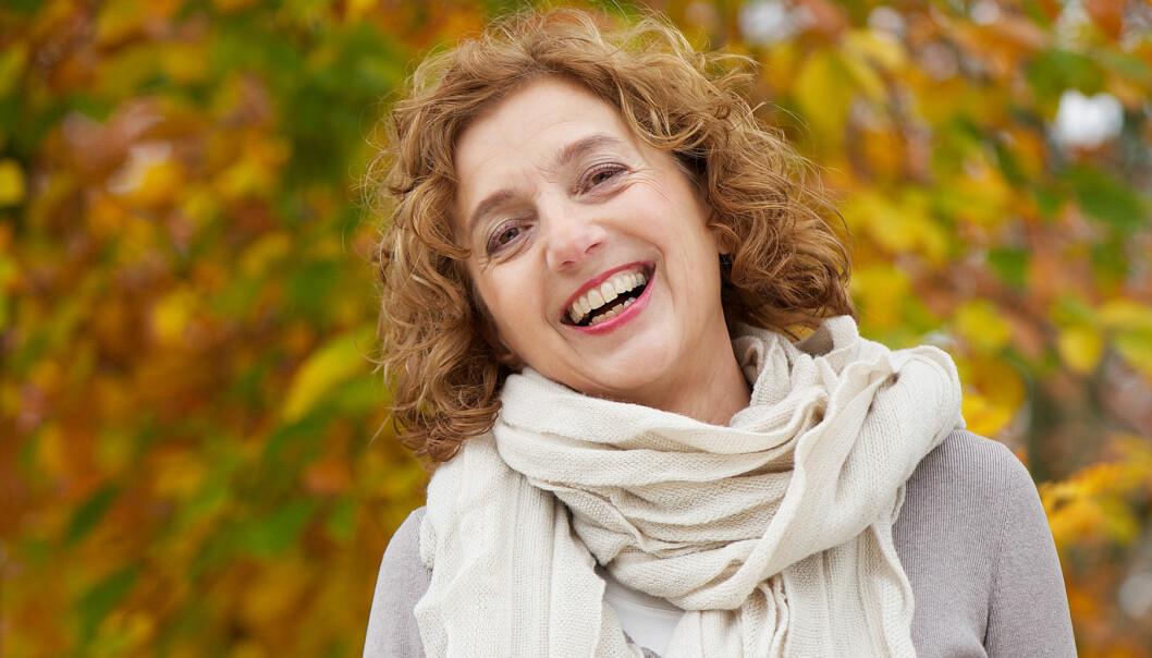 Glad kvinna med höstig bakgrund